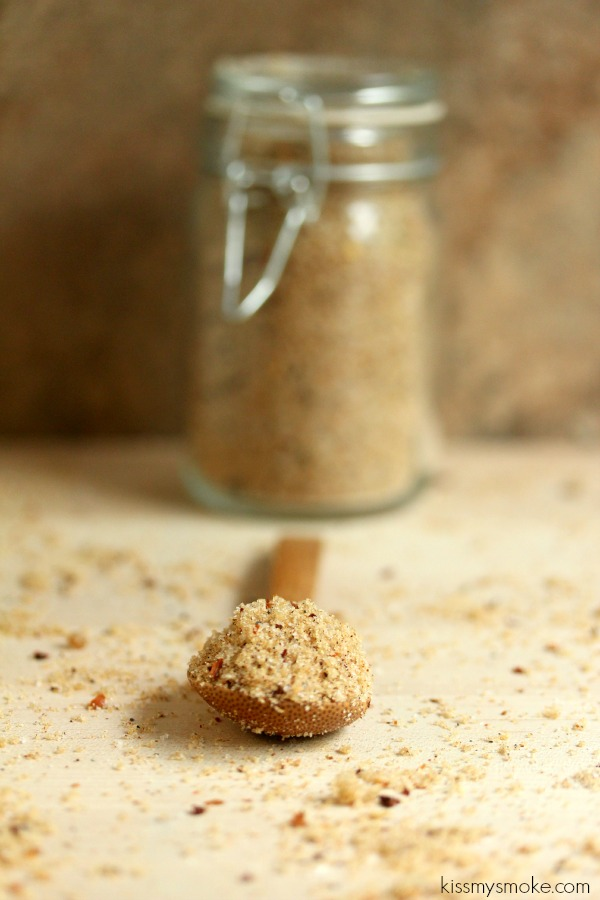 Bring da Heat Dry in a glass spice jar with lid closed in the background. In the foreground is a wooden spoon with the dry rub in it and dry rub scattered on a light coloured surface.