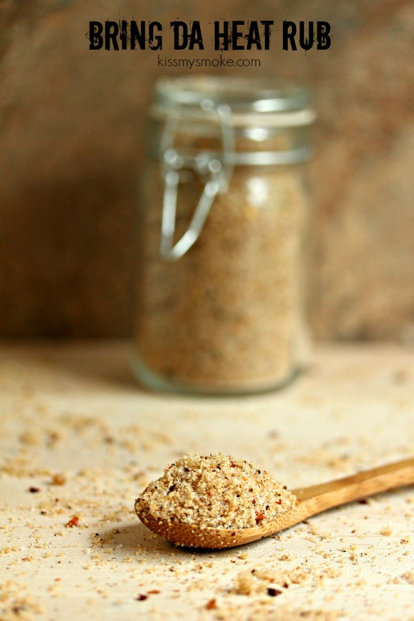 Bring Da Heat Dry Rub is in a glass spice jar in the background with a wooden spoon holding some spice in the foreground, spice is scattered about and text at top states the recipe and blog name.