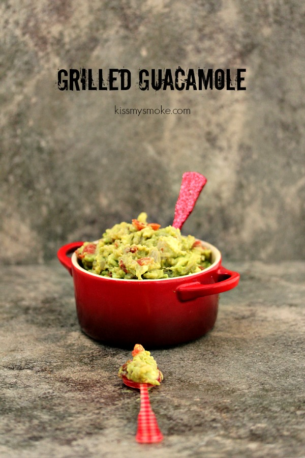 Grilled Guacamole served in a red dish with a red spoon