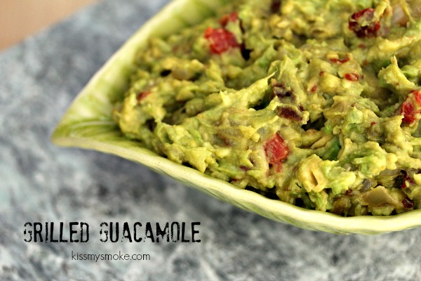 Grilled Guacamole served in a green bowl on a grey counter.