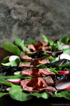 Grilled steak salad loaded with greens, radish and steak, all covered in a drizzle of balsamic sauce. Plate in on a dark counter with a dark background.
