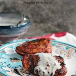 Slow Grilled Chicken Thighs with Alabama White Sauce served on a white and blue plate with a bowl of sauce in the background