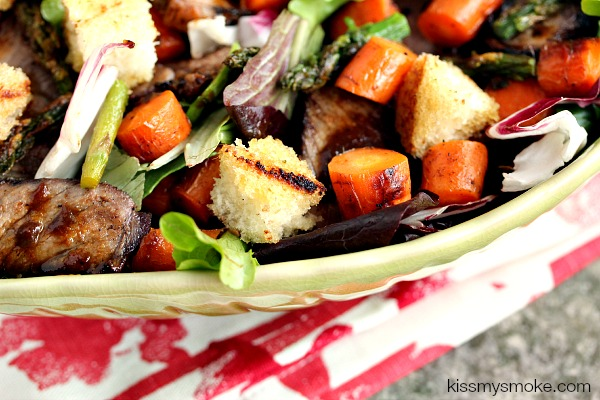 grilled steak salad in a green bowl on a red and white napkin