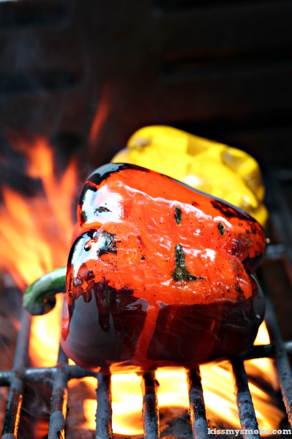 Fire Roasted Bell Peppers on a hot grill with flames shooting up around the red and yellow pepper.