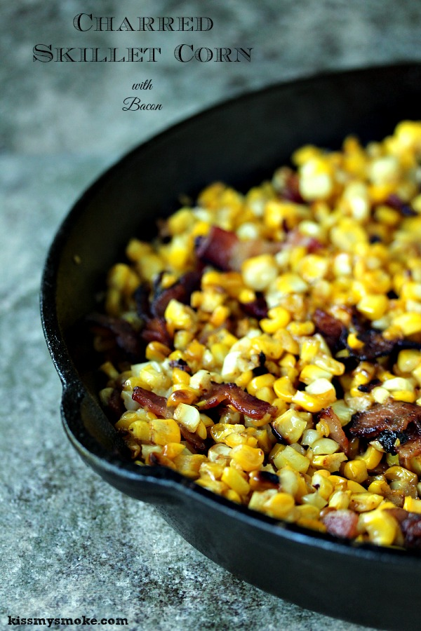 Charred skillet corn with bacon in a black cast iron pan on a tile counter.