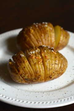 Cooked garlic hasselback potatoes on a white plate.