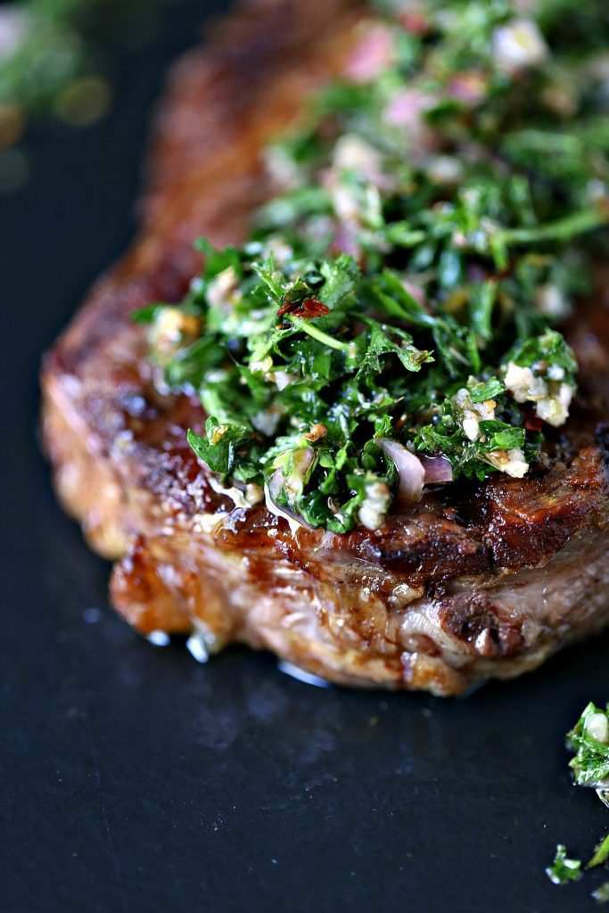 Grilled Rib Steaks with Chimichurri Sauce served on a black platter!