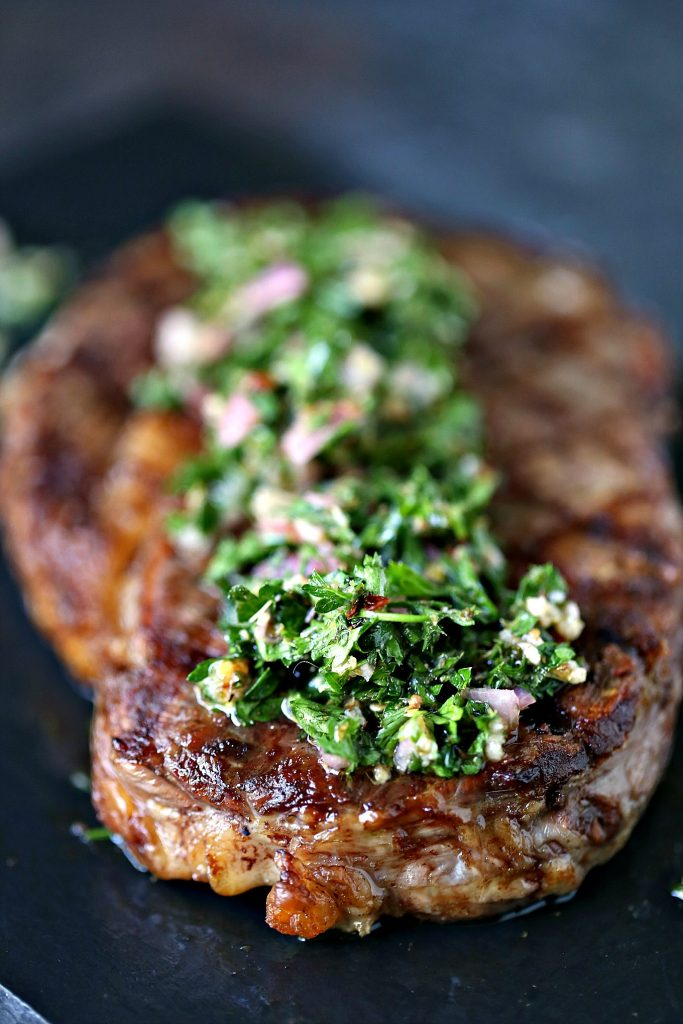 Grilled Rib Steaks with Chimichurri Sauce served on a black platter for dinner.