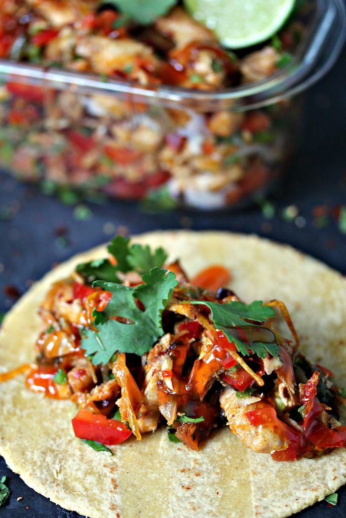 Grilled Chicken Fajita Foil Packs served on tortillas with a container of the fajita filling in the background.