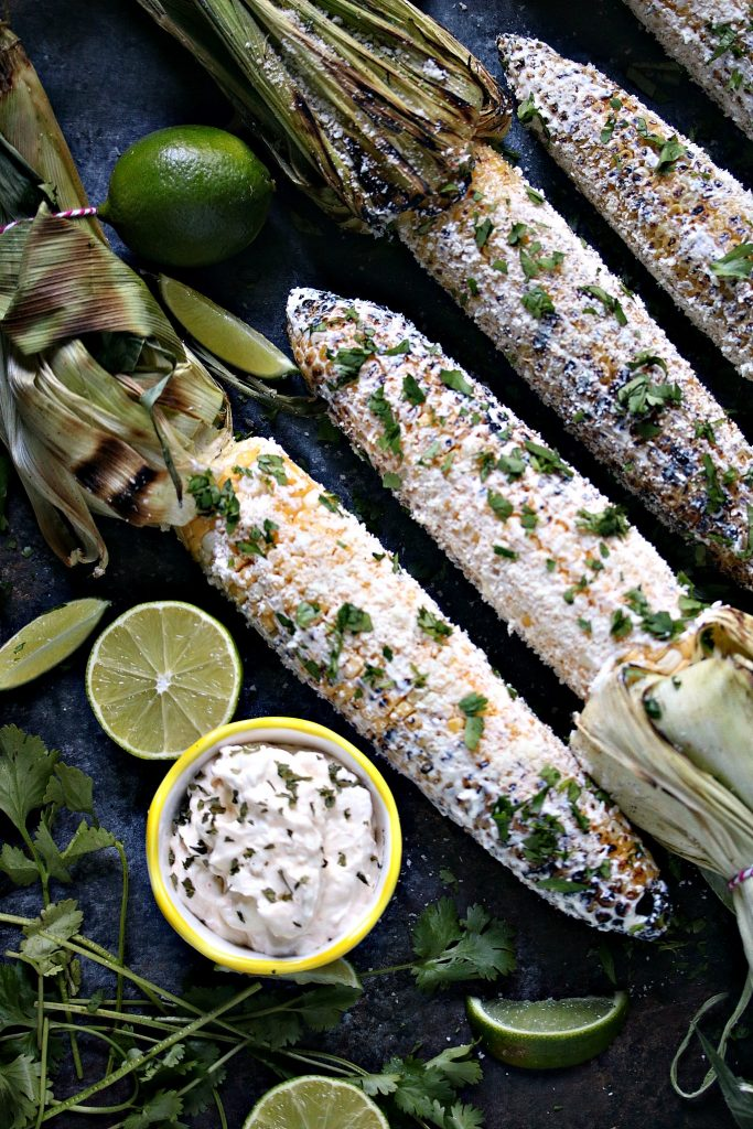 Grilled Mexican Street Corn (Elotes) on a dark counter served with extra garnishes.