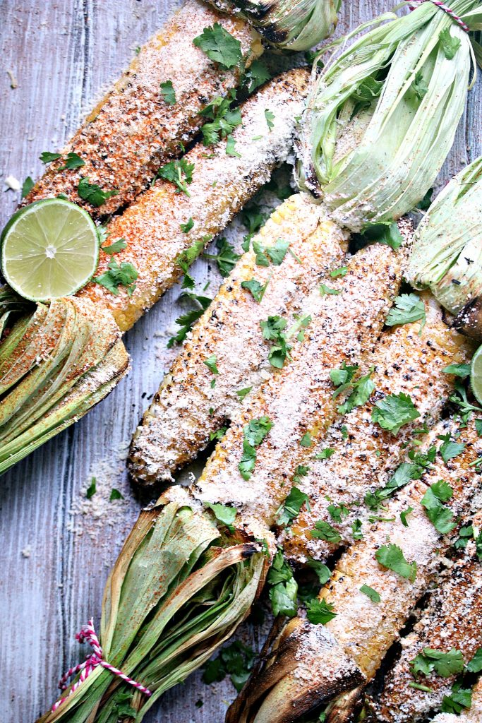 Grilled Mexican Street Corn (Elotes) from kissmysmoke.com- This Mexican Street Corn is grilled over charcoal then slathered with creamy goodness, sprinkled with delicious cheese, and garnished with cilantro and limes.