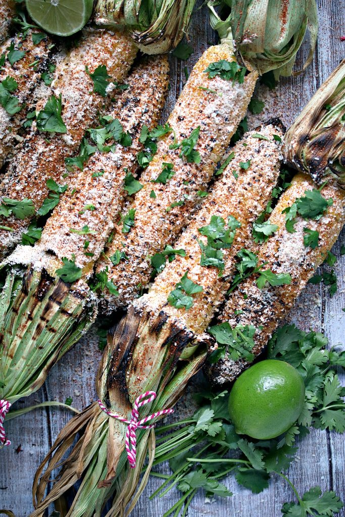 Grilled Mexican Street Corn (Elotes) garnished with cilantro and lime.