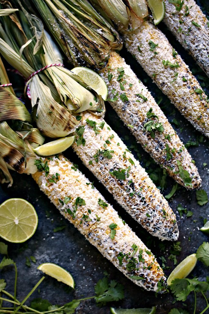 Grilled Mexican Street Corn (Elotes) being serves with extra lime and cilantro!