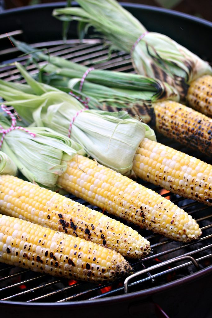 Grilled Mexican Street Corn (Elotes) on a charcoal grill.