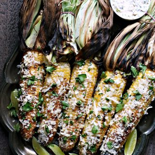 Grilled Mexican Street Corn from kissmysmoke.com- This Mexican Street Corn is grilled over charcoal then slathered with creamy goodness, sprinkled with delicious cheese, and garnished with cilantro and limes.